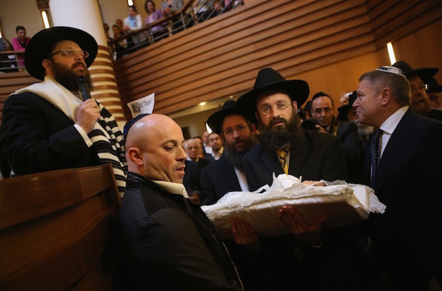 An infant being carried before his circumcision at an Orthodox synagogue in Berlin in 2013. (Sean Gallup/Getty Images)