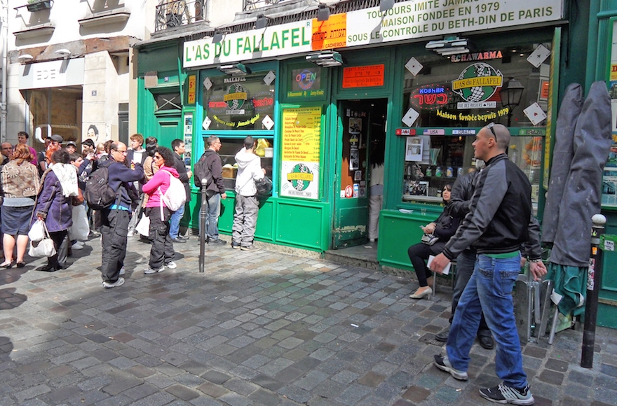 Yomi Peretz, right, approaching a line of tourists waiting to place their order at L'As Du Fallafel in Paris's historic Jewish quarter in April 2012. (WikiMedia Commons)