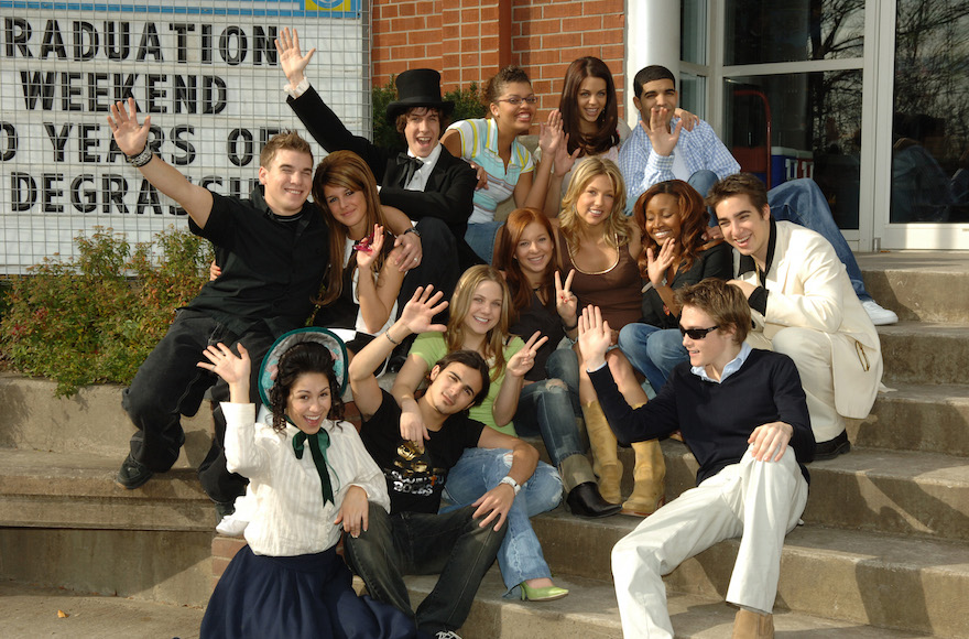 The cast of 'Degrassi: Next Generation' celebrating their 100th episode at the Degrassi High School Set in Toronto, Canada. Drake is at the top right, Lauren Collins is in center in green shirt, Jake Goldsbie is on right in white jacket, Shane Kippel is far left in black shirt. (George Pimentel/WireImage)