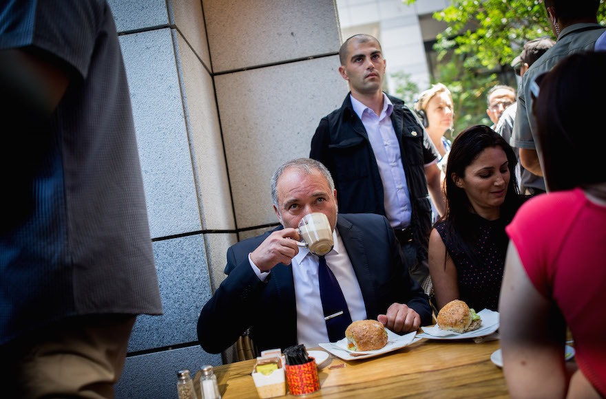 Defense Minister Avigdor Liberman drinking coffee at Sarona Market in Tel Aviv, a day after a deadly attack at the pedestrian mall, June 9, 2016. (Miriam Alster/Flash90)
