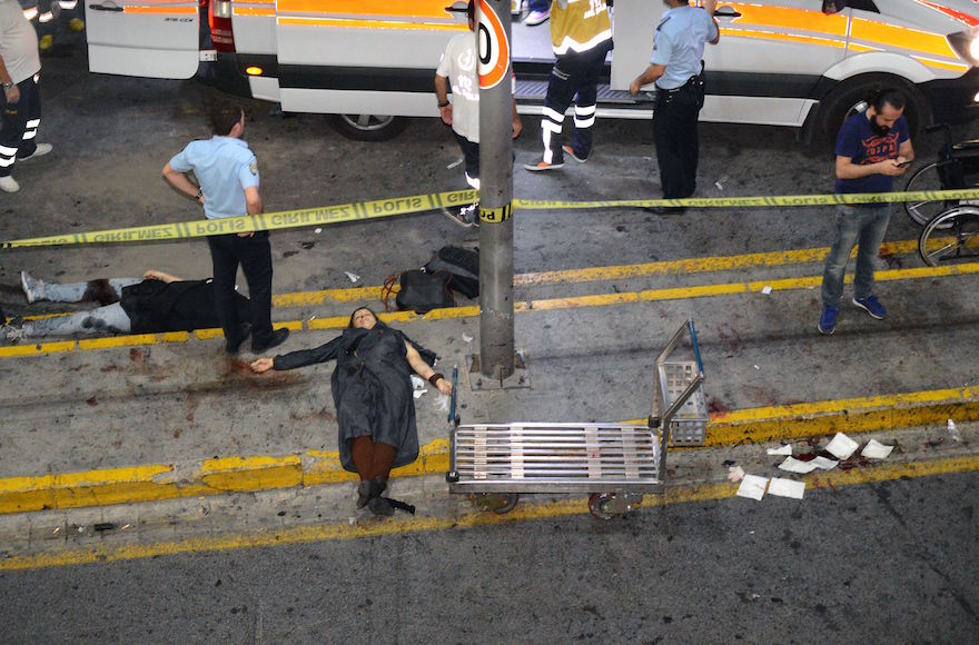 EDITORS NOTE: Graphic content / This picture obtained from the Ilhas News Agency shows ambulances and police intervening next to injured people lying on the ground, after two explosions followed by gunfire hit the Turkey's biggest airport of Ataturk in Istanbul, on June 28, 2016. At least 10 people were killed in a suicide attack at the international terminal of Istanbul's Ataturk airport, June 28, 2016. (AFP/Getty Images)
