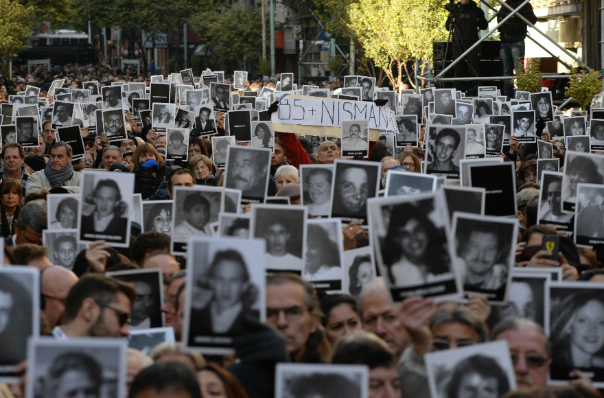 Participants in a memorial ceremony on the 22nd anniversary of the AMIA Jewish Center bombing in Buenos Aires hold photos of some of the 85 victims on July 18, 2016. (Photo by Leonardo Kremenchuzky courtesy of AMIA)