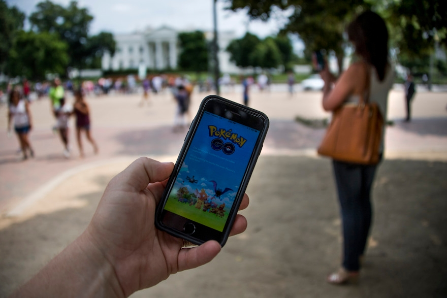 A man holds up his cell phone with a screen shot of the Pokemon Go game as a woman searches on her cell phone for a Pokemon in front of the White House in Washington, DC, July 12, 2016. ( Jim Watson /AFP/Getty Images)