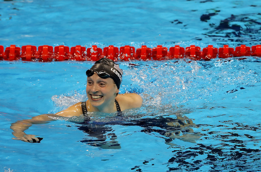 Katie Ledecky celebrating winning gold and setting a new world record in the Women's 400-meter freestyle final on day two of the Rio 2016 Olympic Games at the Olympic Aquatics Stadium, Aug. 7, 2016. (Al Bello/Getty Images)