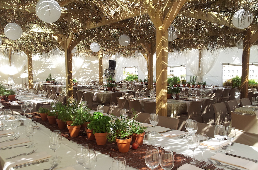 A 2012 sukkah from Studio Ya Ya for the Bible Lands Museum aims to take visitors back to ancient times, infusing temporary structure with natural woods and fresh herbs. (Courtesy of Yarok Yarok Events Design)
