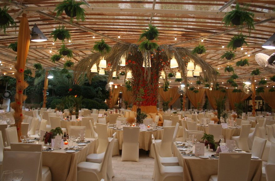 The sukkah designed by Studio Ya Ya in 2010 for the Inbal Jerusalem Hotel employed a massive, palm tree centerpiece threaded with tiny red flowers. (Courtesy of Yarok Yarok Events Design)