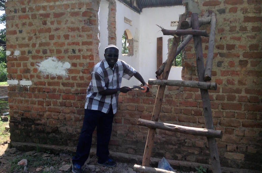 Rabbi Gershom Sizomu, leader of Uganda's Jewish community, dismantling the old synagogue in Nabagoye. (Courtesy of Be'chol Lashon)
