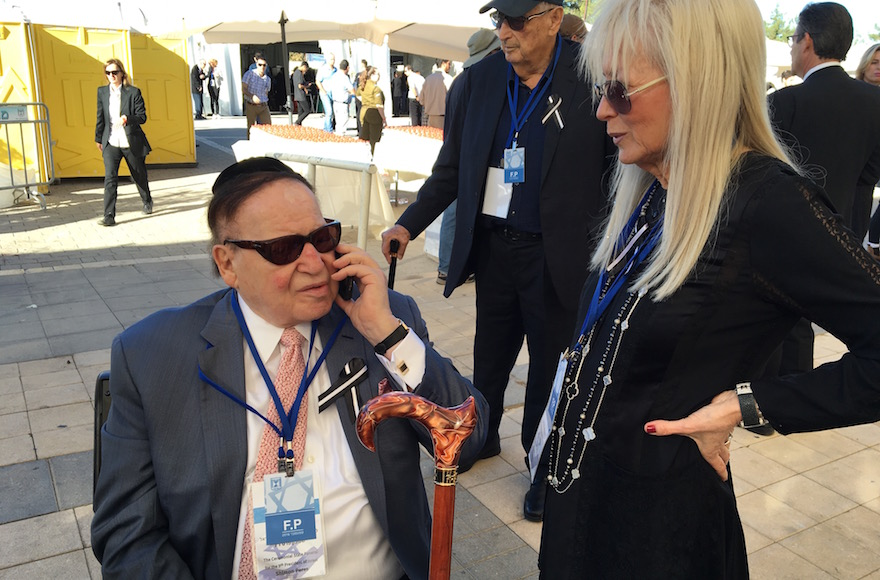 Sheldon Adelson speaking with Army Radio by phone at the funeral of Shimon Peres at Mount Herzl national cemetery in Jerusalem, Sept. 30, 2016. (Andrew Tobin)