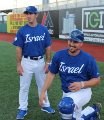 Catcher Ryan Lavarnway, who socked three singles, enjoys a moment during pregame warmups with Israel's bullpen coach Alon Leichman, in Brooklyn, New York, Sept. 22, 2016. (Hillel Kuttler)