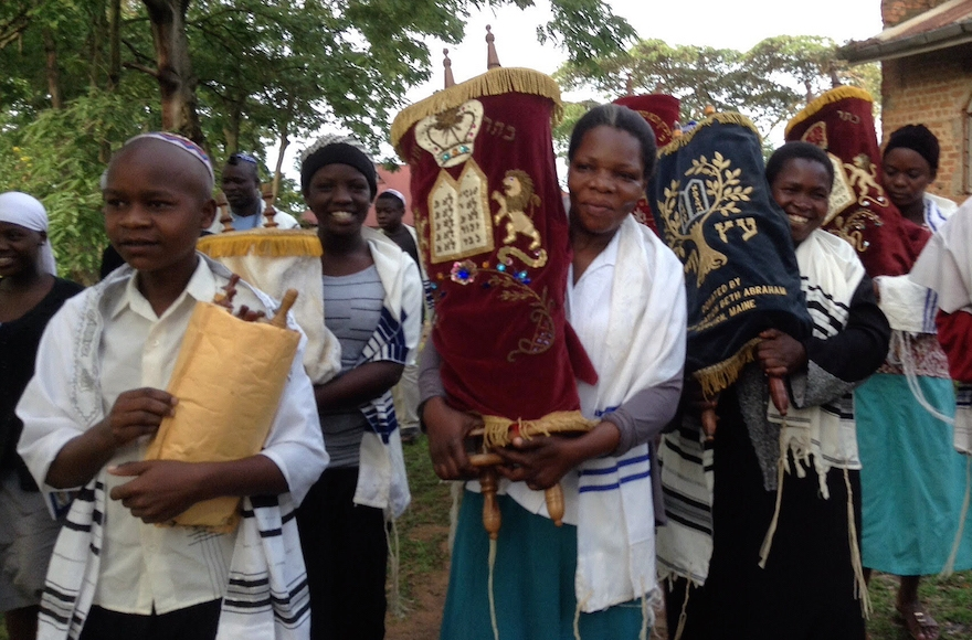 In anticipation of the construction of a new synagogue in Nabagoye, Uganda, the women and children were given the honor of transferring the Torahs from the old synagogue to a temporary home. (Courtesy of Be'chol Lashon)