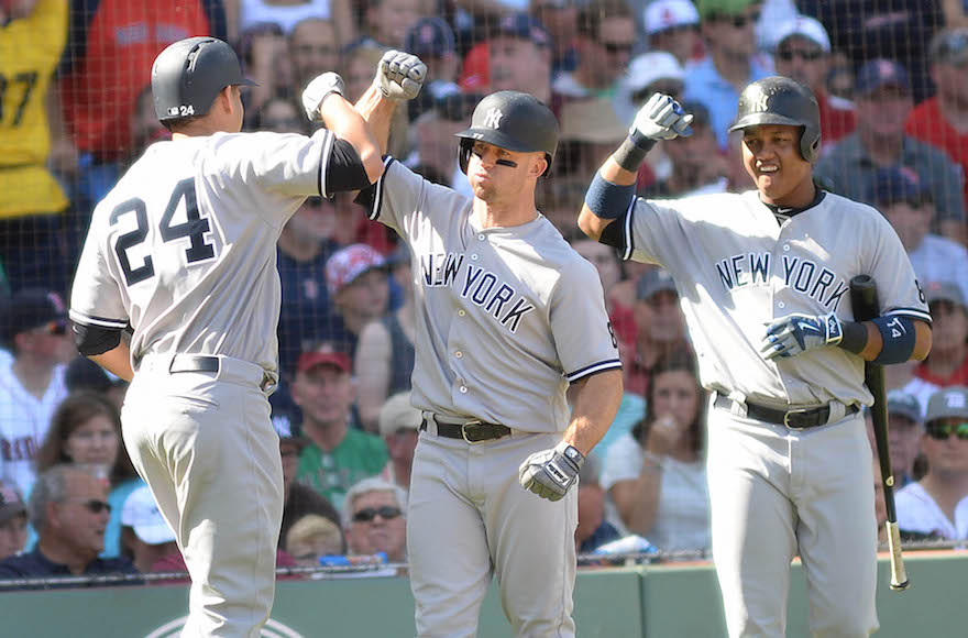 Gary Sanchez, left, high-fiving teammates Brett Gardner, center, and Starlin Castro at a game against the Boston Red Sox at Fenway Park, Sept. 17, 2016. (Darren McCollester/Getty Images)