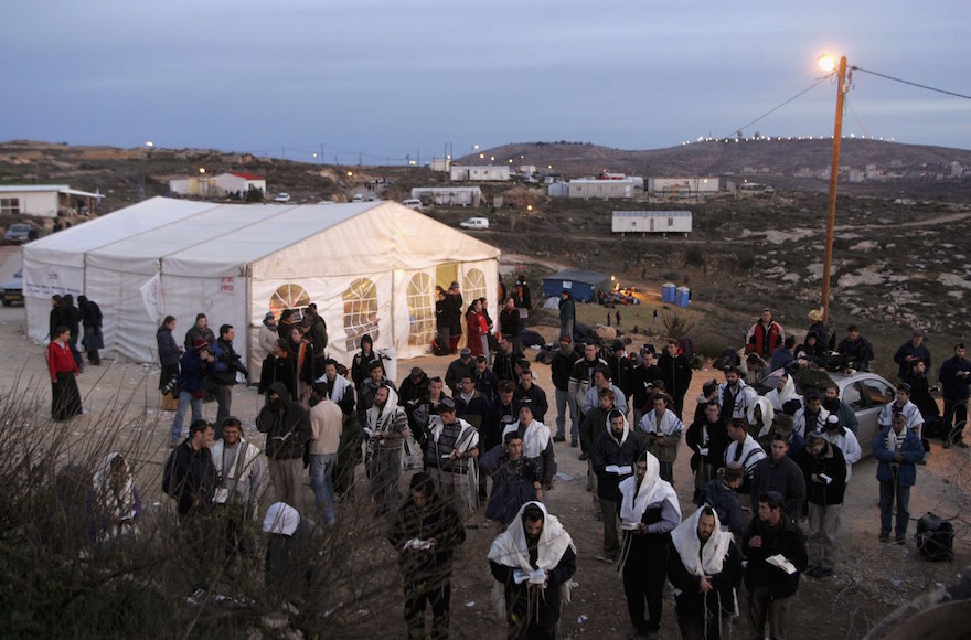 Israeli settlers praying in the West Bank settlement of Amona, Feb. 1, 2006. (Uriel Sinai/Getty Images)