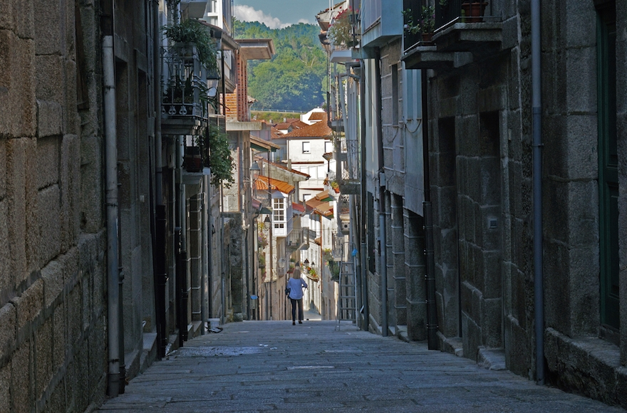 A tourist walking down the historic Jewish Quarter of the town of Ribadavia in Spain, Sept. 26, 2016. (Cnaan Liphshiz)