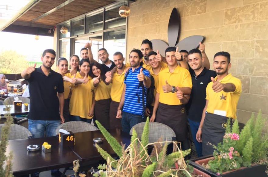 Owner John Saaden posing with members of his staff outside Jasmine Cafe in Nablus, West Bank. (Facebook)