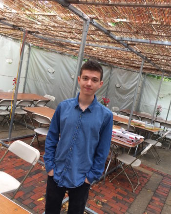 Gabe Hodgkin, a sophomore at Harvard, in the sukkah at Harvard Hillel. Designed by Moshe Safdie, the building's courtyard was designed to accommodate a sukkah. (Penny Schwartz)