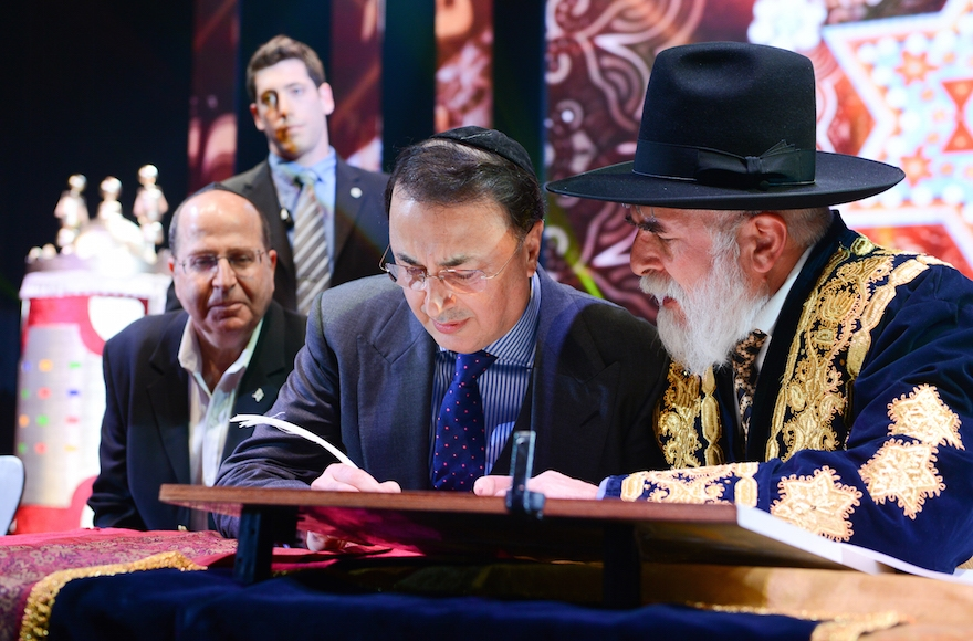 Lev Leviev, center, writing in a Torah scroll with Rabbi Eliyahu Yaakov, right, and Israel's then defense minister Moshe Yaalon in Jerusalem, March 23, 2014. (Israel Barddougo/World Congress of Bukhara Jews)