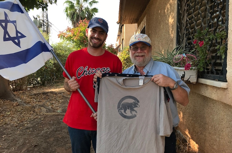 Harel Gold (left) and Rabbi Sidney Gold displaying their Cubs gear outside their home in Karnei Shomron in the West Bank, Oct. 28, 2016. (Andrew Tobin)