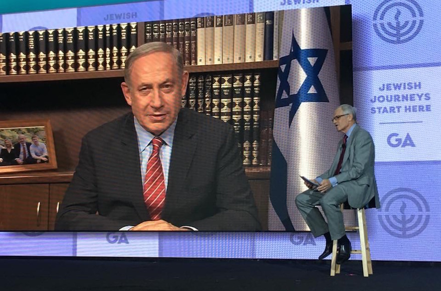 Israeli Prime Minister Benjamin Netanyahu, on screen, being interviewed by Richard Sandler at the JFNA General Assembly, Nov. 15, 2016. (Ron Sachs)
