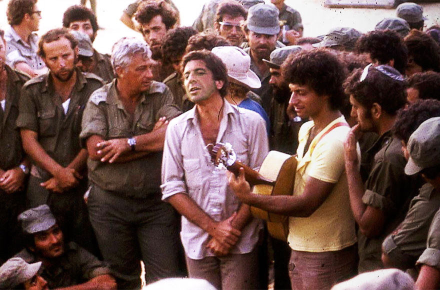 Leonard Cohen, center, performing with Mati Caspi, on guitar, for Ariel Sharon and other Israeli troops in Sinai in 1973. (Courtesy of Ma'ariv)