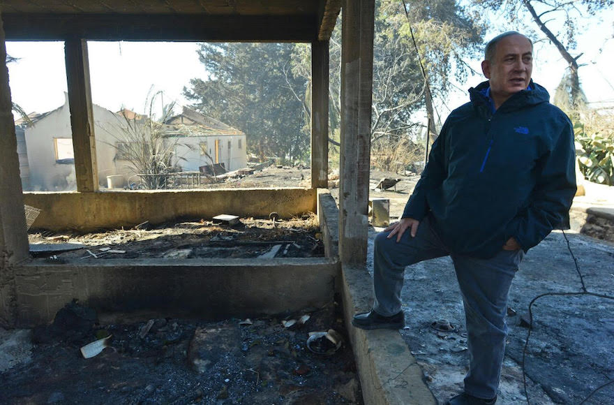 Israeli Prime Minister Benjamin Netanyahu standing next to damage caused by fire in Israel (Kobi Gideon/Prime Minister's Office)