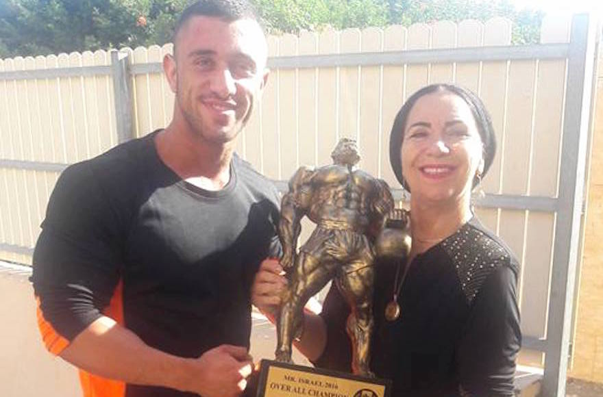 Kobi Yifrach, left, and his mother, Ruti Yifrach, holding the Mr. Israel trophy, 20 of Kobi Yifrach)
