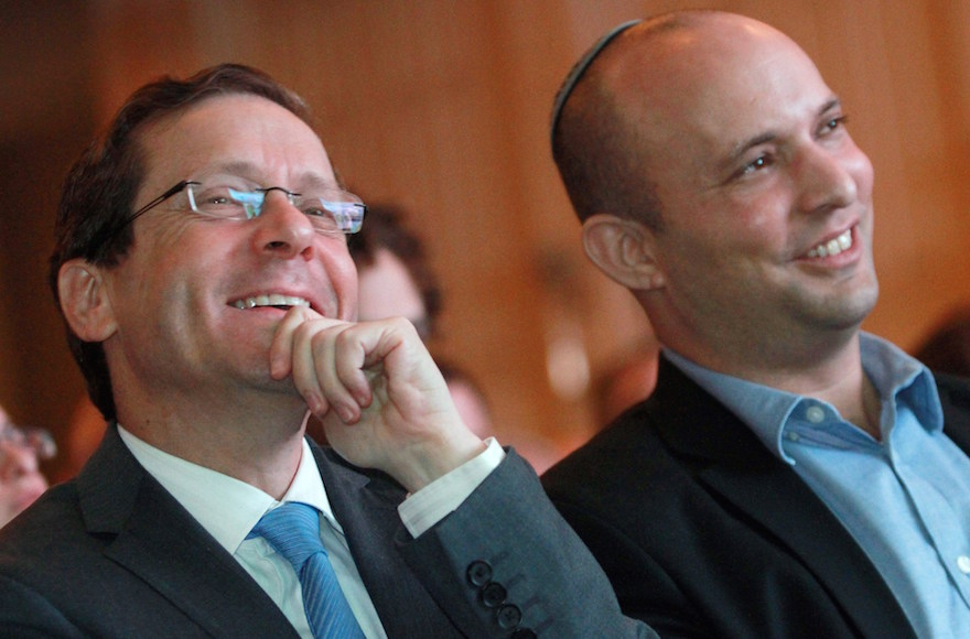 Israeli Labor Party leader Isaac Herzog, left, and head of the Jewish Home party Naftali Bennett listening during a debate on the economy in Tel Aviv, March 11, 2015. (Gil Cohen Magen/AFP/Getty Images)