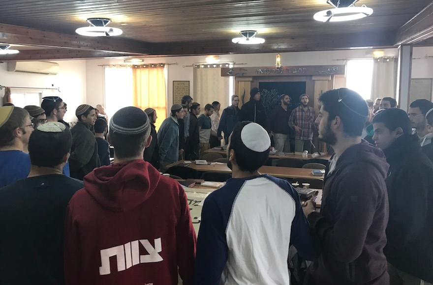 Young men dancing and singing in the synagogue in Amona, the West Bank, Dec. 13, 2016. (Andrew Tobin)