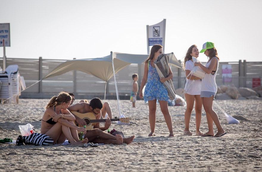 Israelis enjoying the warm weather on the beach in Tel Aviv, Oct. 3, 2016. (Nati Shohat/Flash90)