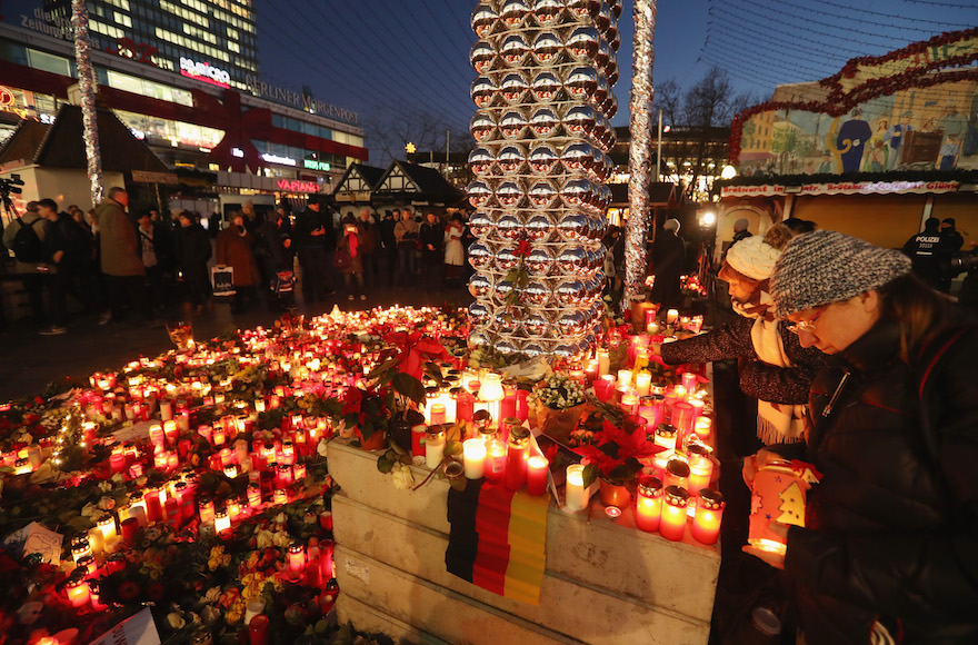 Mourners laying flowers and candles at a makeshift memorial near the site where two days before a man drove a heavy truck into a Christmas market in an apparent terrorist attack in Berlin, Germany, Dec. 21, 2016. (Sean Gallup/Getty Images)