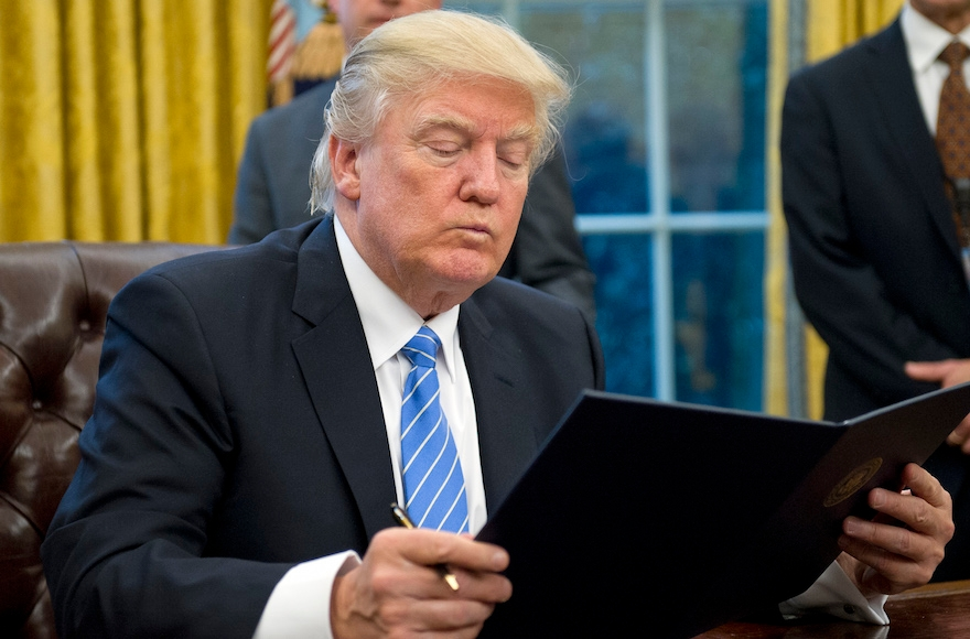 President Donald Trump reading the first of three Executive Orders he will sign in the Oval Office, Jan. 23, 2017. (Ron Sachs/Pool/Getty Images)
