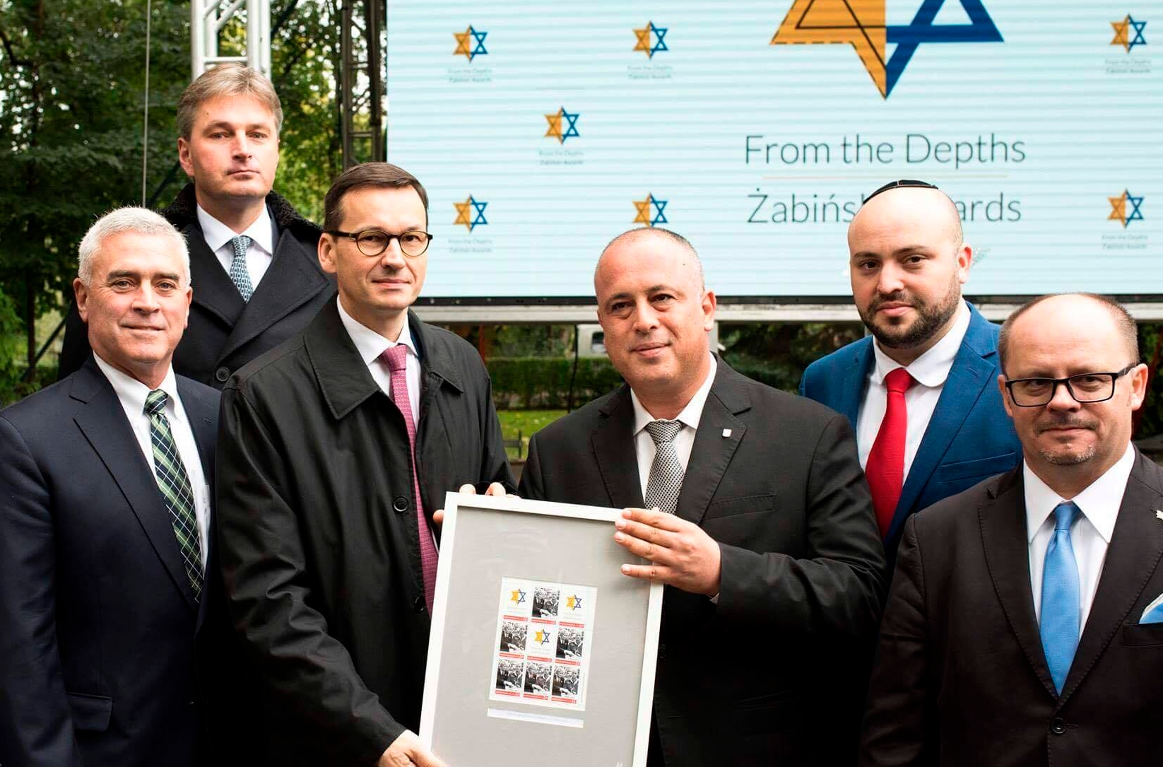 Mateusz Morawiecki 3rd from left holding a document honoring rescuers of Jews at Warsaw Zoo on Sept 18 2017 Courtesy of From the Depths