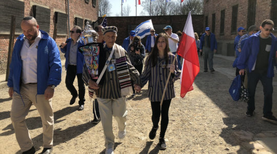Edward Mosberg, holding a Torah scroll, during March of the Living in 2017 at the former death camp Auschwitz in Poland. (Courtesy of From the Depths)