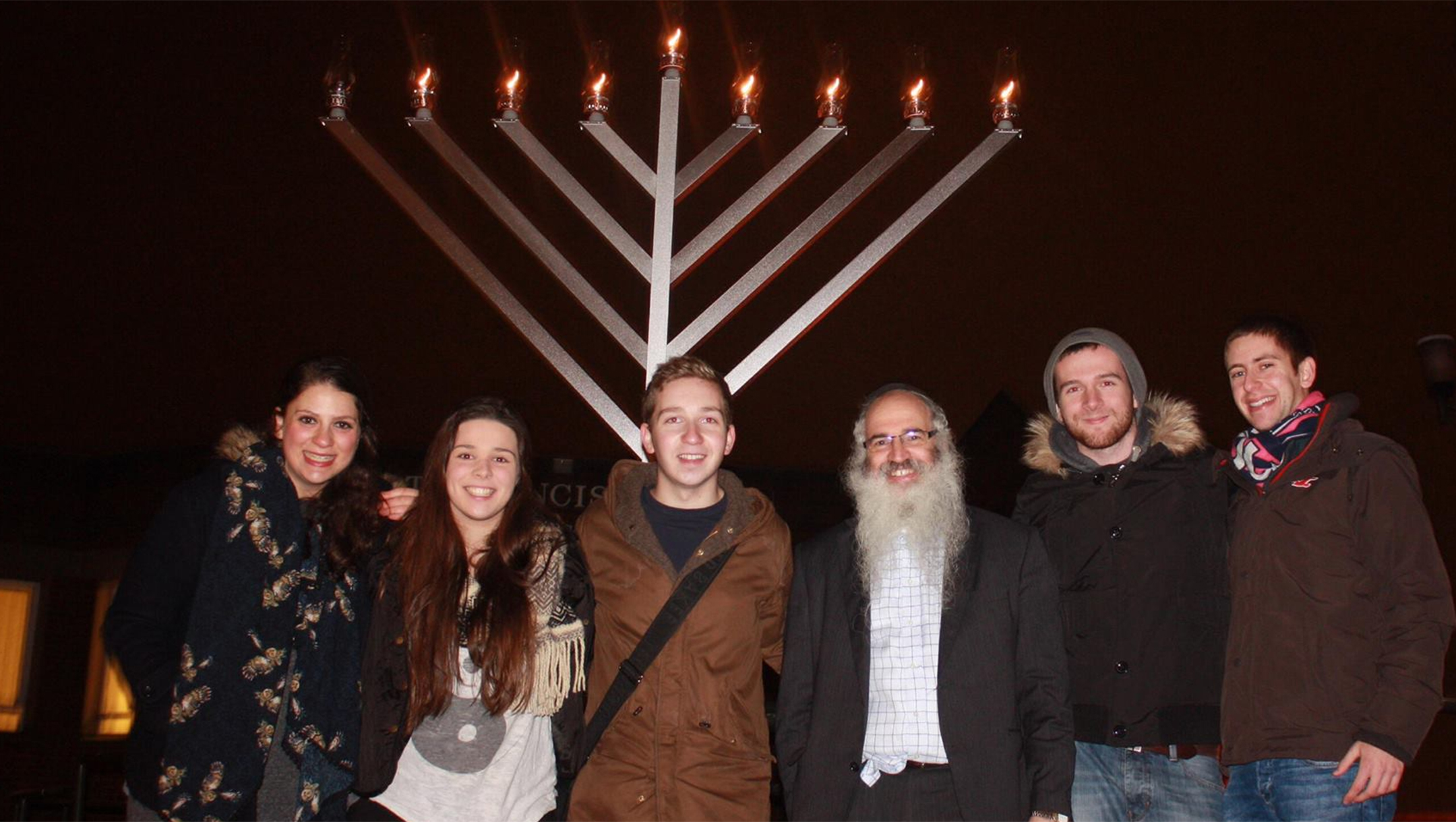 Rabbi Fishel Cohen with Jewish students at a candle lighting ceremony in Hanukka in Birmingham, the United Kingdom on Dec. 24, 2014. (Courtesy of Rabbi Fighsel Cohen /The Birmingham Tab)