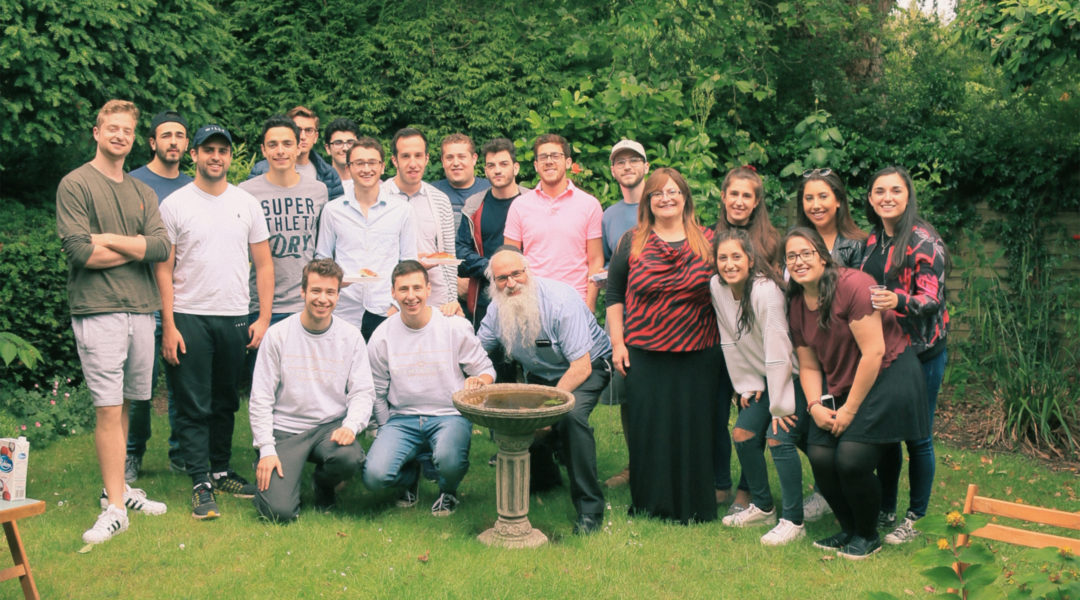 Rabbi Fishel Cohen, wearing a kippah, and his wife Esther with Birmigham university students at the local Hillel House in July 2018. (Courtesy of Rabbi Cohen)