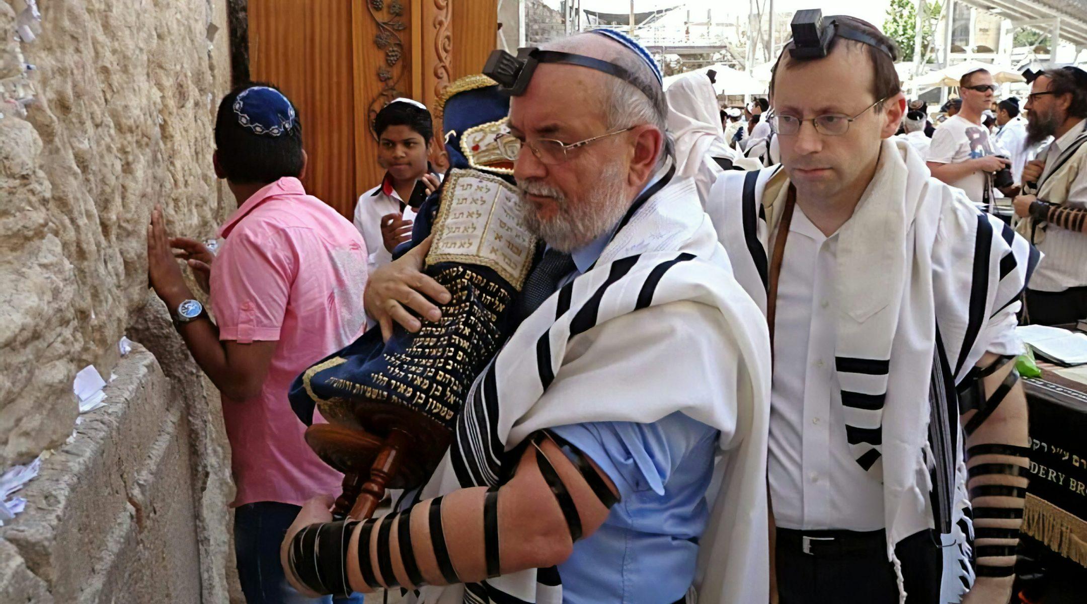 Mariusz Robert Opałko, holding a Torah scroll, and Michael Freund at the Western Wall in Jerusalem, Israel on June 9, 2013. (Courtesy of Shavei Israel)