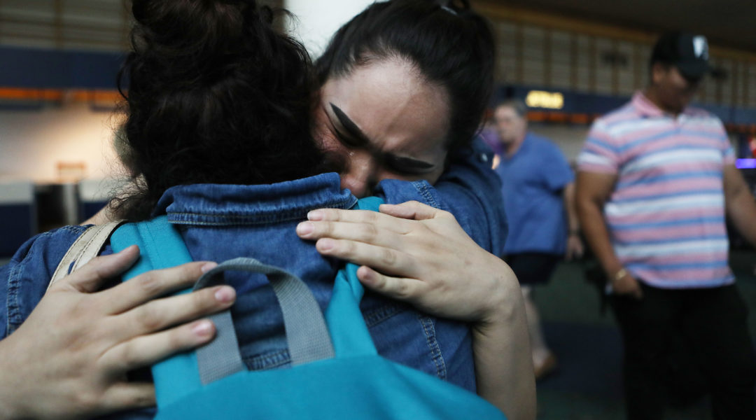 An immigrant recently released after spending six months in an ICE detention facility, is hugged by her daughter while being reunited with family at Portland International Airport on September 2, 2018. (Mario Tama/Getty Images)