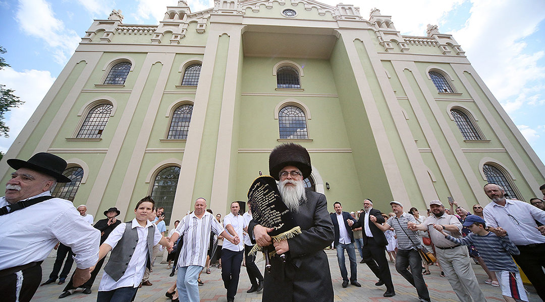 Yaakov Dov Bleich carrying a Torah scroll into the synagogue of Drohobycz, Ukraine on July 3, 2019. (Rephael Isaak Vilenskiy)