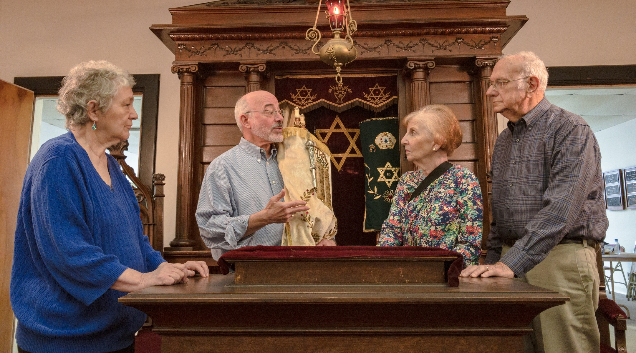 The four members of Temple Mishkan Israel -- Hanna Berger, Ronnie Leet, Joanie Gibian Looney and Charles Pollack --standing in front of the Torah Ark. The synagogue has not held weekly services for decades. (Amy Milligan)
