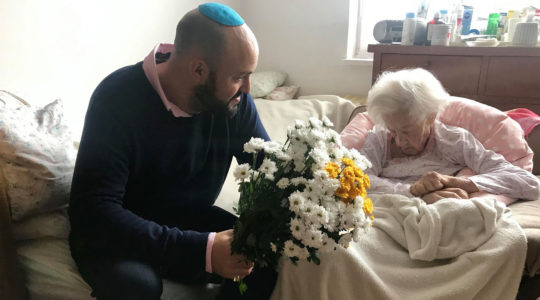 Krystyna Danko receiving flowers from Jonny Daniels on in her apartment in Warsaw, Poland on her 102nd birthday on July 9, 2019. (From the Depths)
