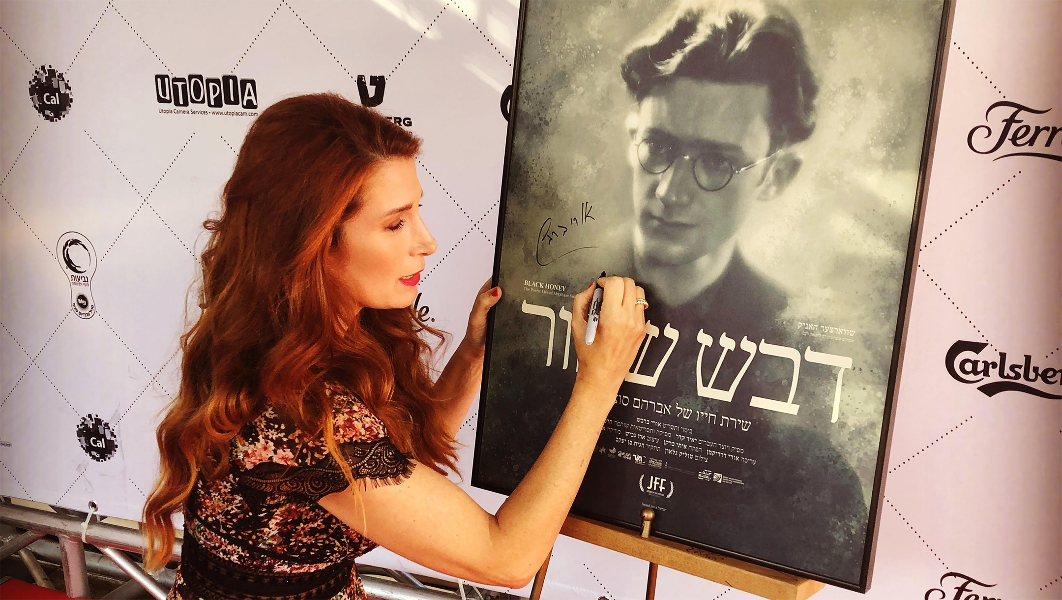 Hadas Kalderon-Sutzkever signing a poster for a new film about her grandfather Abraham Sutzkever in 2018 in Tel Aviv. Courtesy of Kalderon-Sutzkever