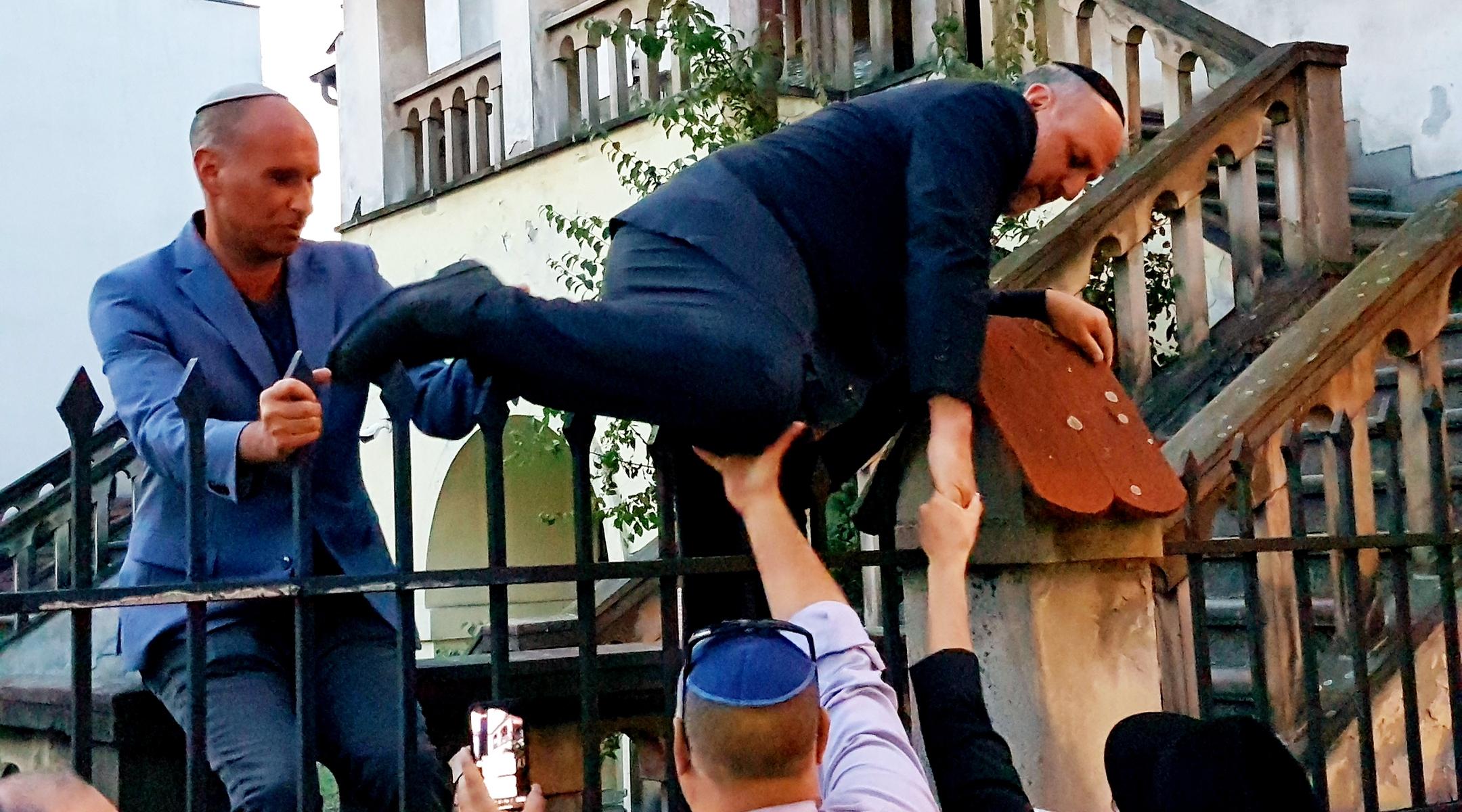 Le rabbin Michael Schudrich escalade la clôture de la synagogue Izaak barricadée à Cracovie, en Pologne, le 4 juillet 2019. (Shimon Briman)