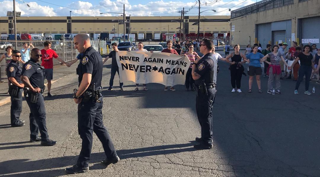 Police stand in front of protestors at a demonstration at an ICE detention center in Elizabeth, N.J. on July 7, 2019. (Naftali Y. Ehrenkranz)