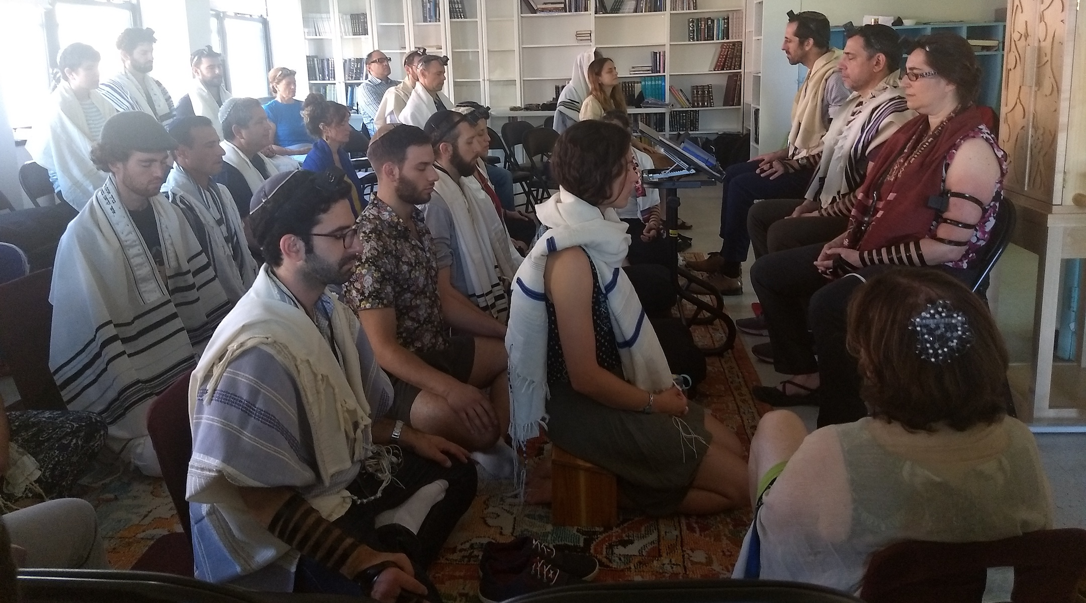 Students meditate as part of the morning prayer at Romemu Yeshiva in New York, N.Y. on July 16, 2019. The yeshiva combines intensive study of Jewish text with mindfulness and mysticism. (Ben Sales)