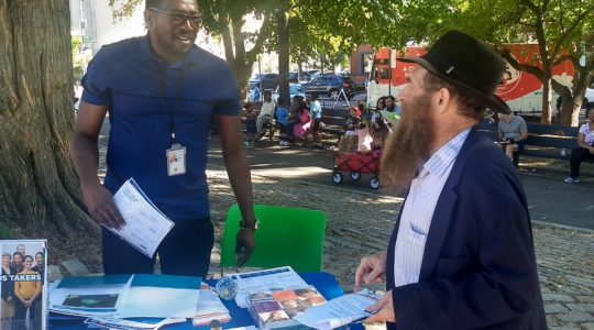 Rabbi Eli Cohen (right), the executive director of the Crown Heights Community Center, talks with a census volunteer at the #OneCrownHeights festival in Brooklyn, New York on Sunday, September 15, 2019. (Ben Sales)