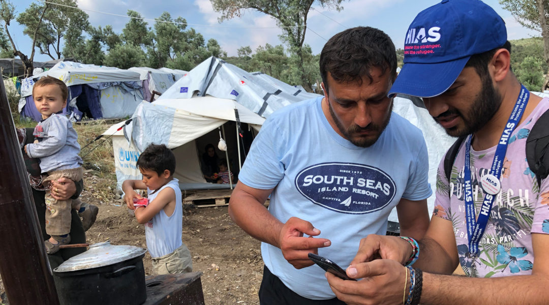 HIAS Greece translator Jalal Barezkai, right, assisting a Syrian refugee in an encampment near the Moria refugee camp on the island of Lesvos, Greece on May 9, 2018. (Bill Swersey/HIAS)
