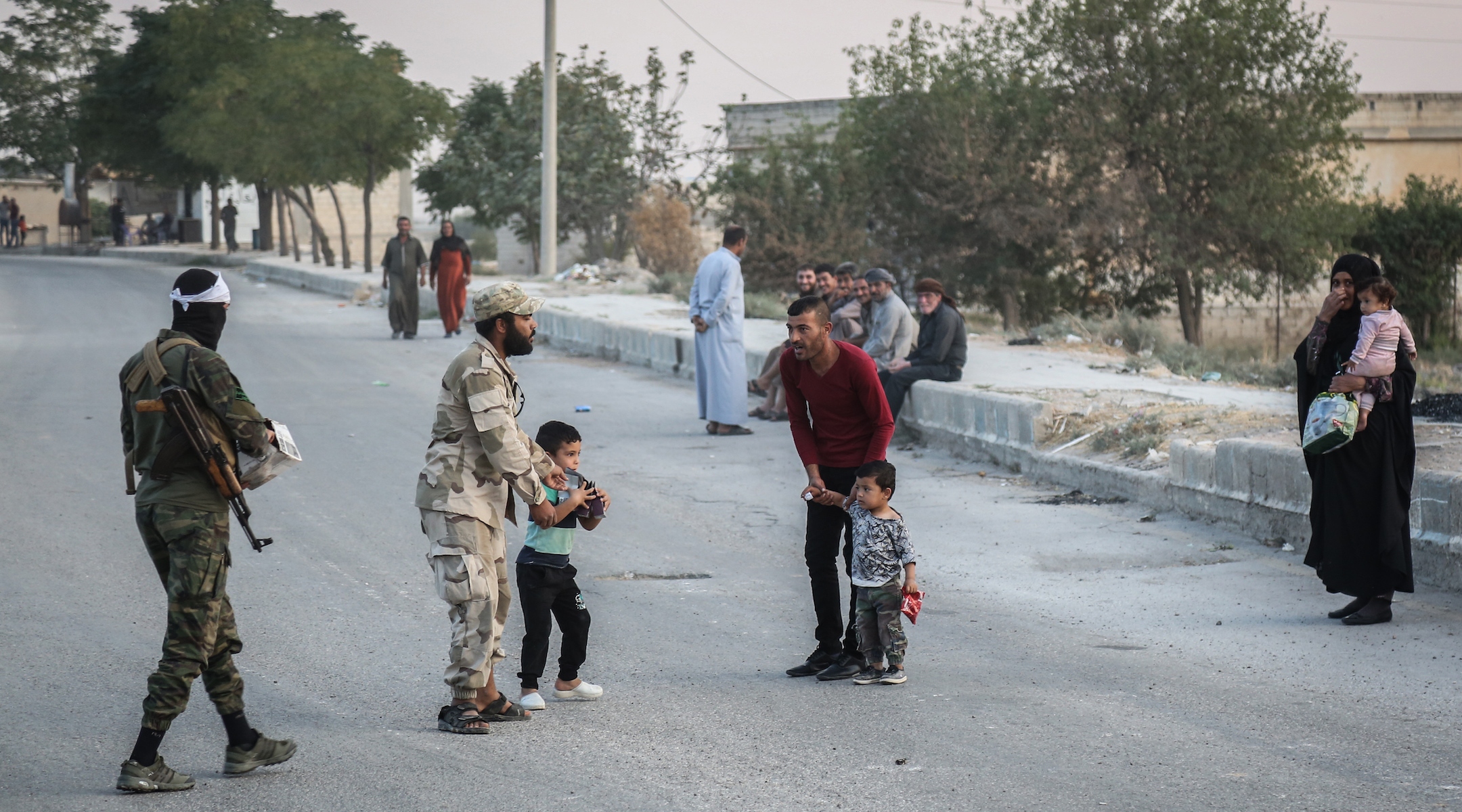 Soldiers of the Turkish-backed Syrian National Army talk to local residents in Tel Abiad, Syria on Oct. 14, 2019. (Anas Alkharboutli/Getty Images)