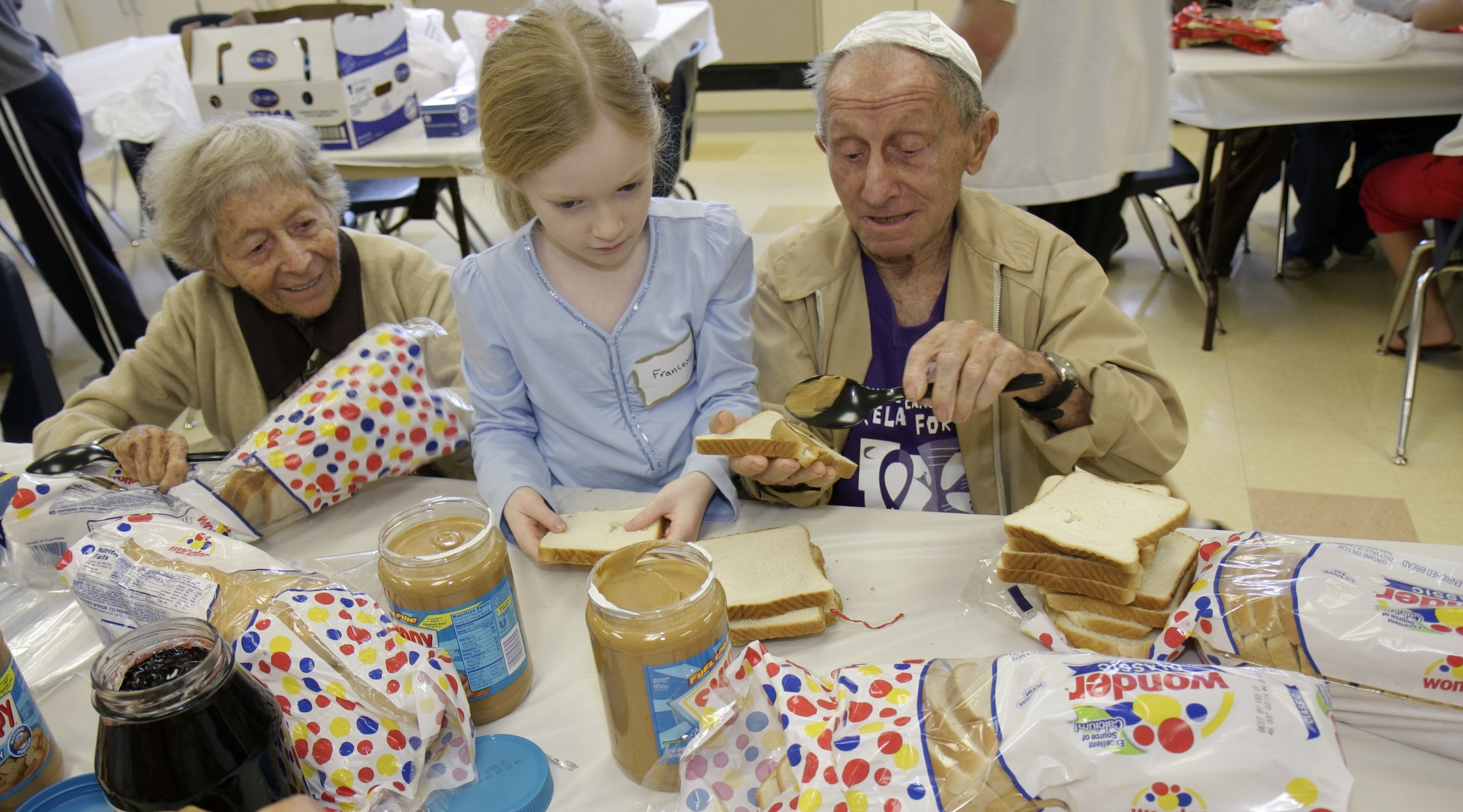 A senior couple and young girl preparing food for the Mitzvah Weekend at a synagogue in 2008. (Jeffrey Greenberg/Getty Images)