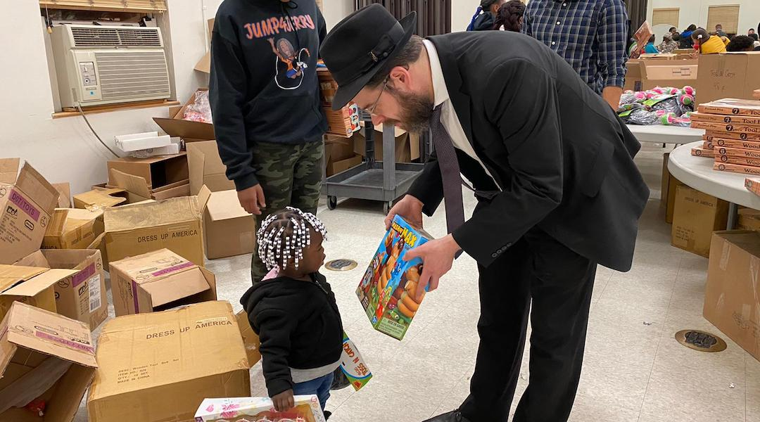 Rabbi Moshe Z. Schapiro shows a toy to a child during the charity drive in Jersey City on December 23, 2019. (Courtesy of Benny Polatseck)