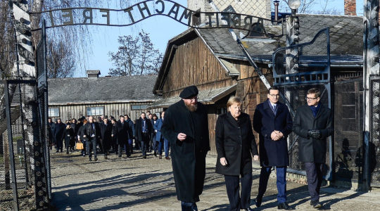 German Chancellor Angela Merkel and Poland's Prime Minister, Mateusz Morawiecki, second from left, receiving a tour by employees of the former Auschwitz Nazi concentration camp near Krakow, Poland on Dec. 6, 2019. (Omar Marques/Getty Images)