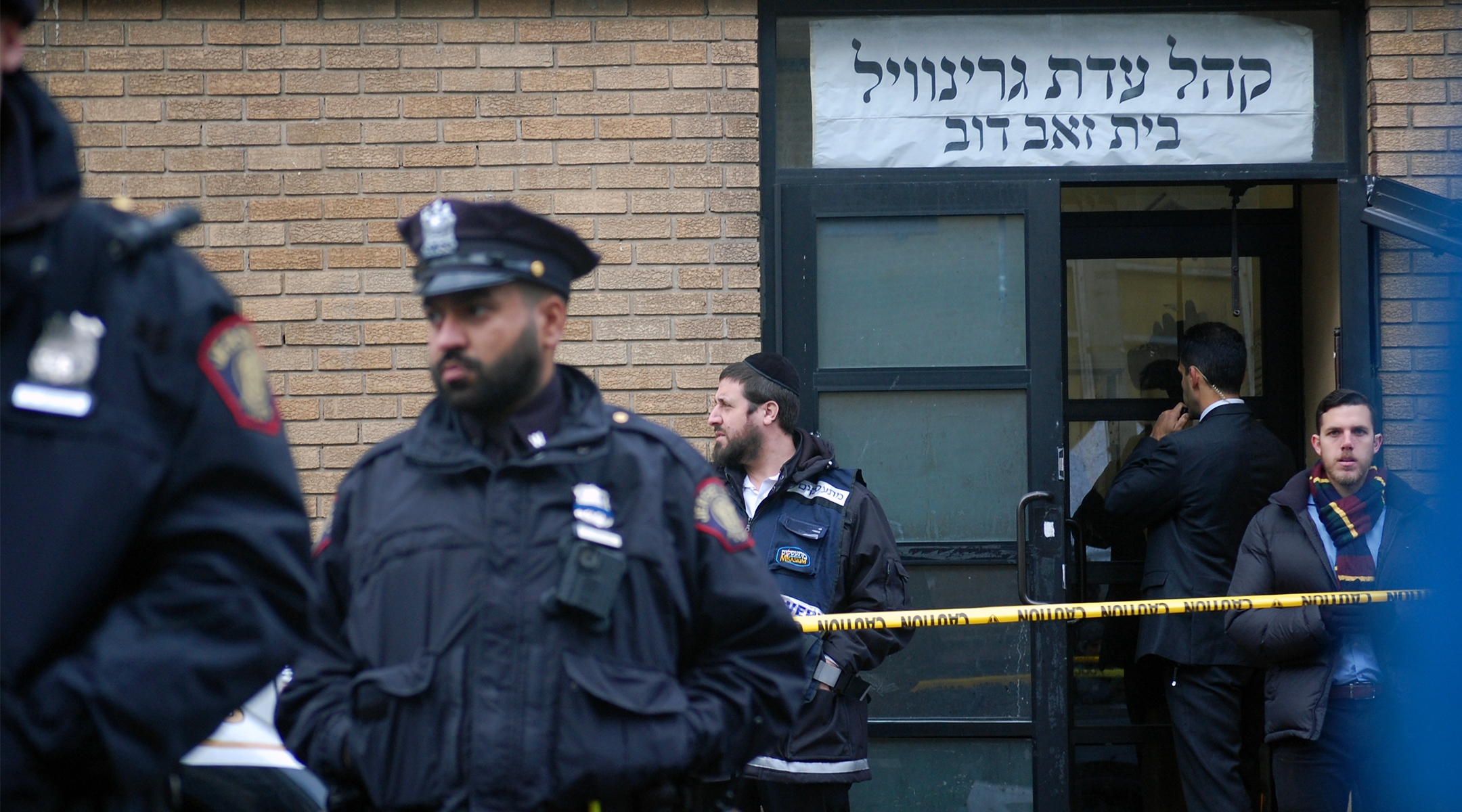 Hasidim, government officials and police officers stand in front of the K'hal Adas Greenville synagogue next door to JC Kosher Supermarket in Jersey City, the site of a deadly shooting, Dec. 11, 2019. (Laura E. Adkins/JTA)